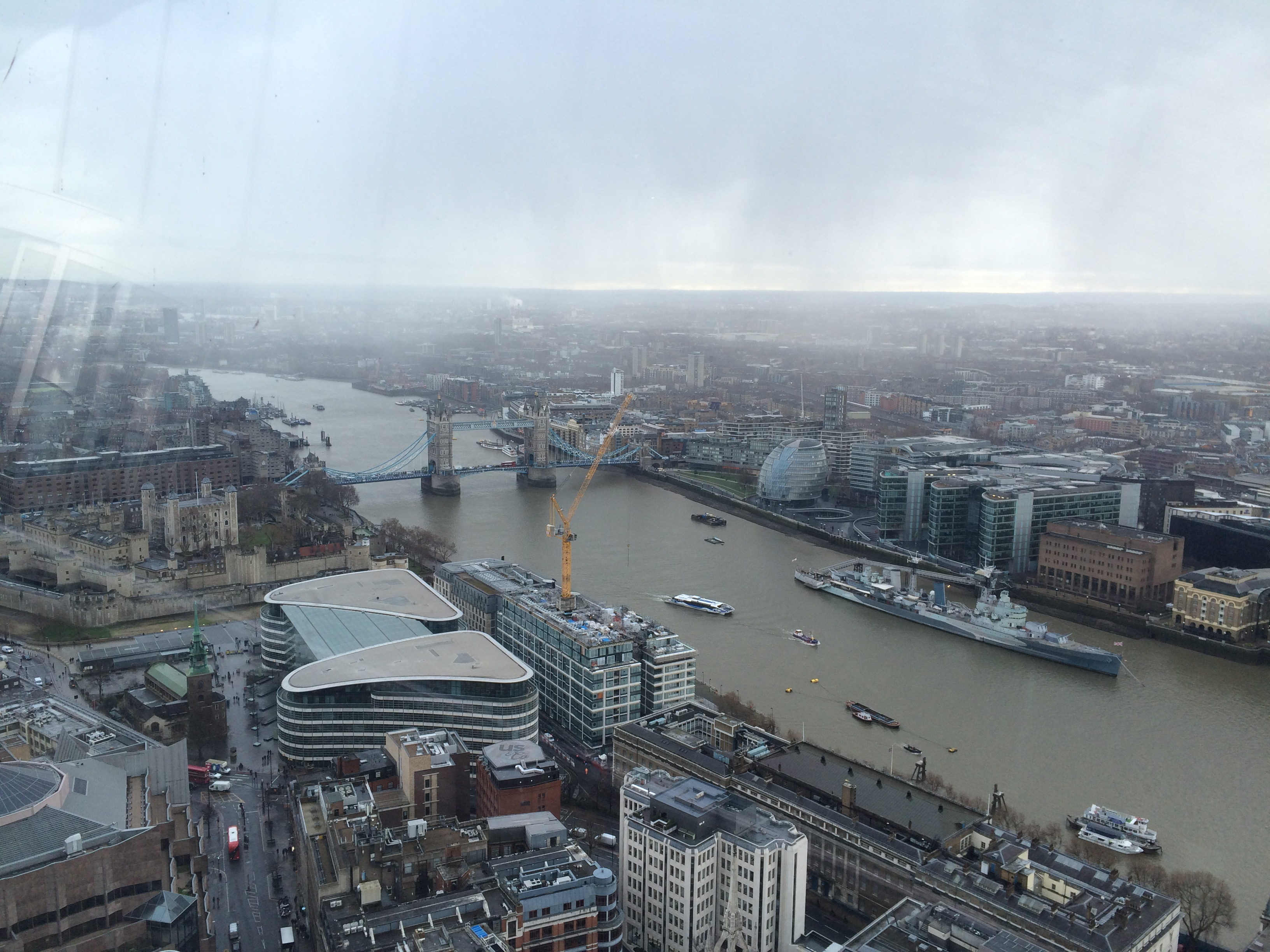 A view of cloudy London's skyline, including the river and Tower Bridge in the background.