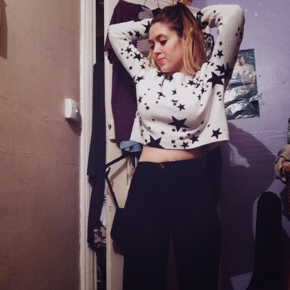 A woman wearing a white jumper with black stars on it, paired with black skinny jeans posing with her arms up behind her head in her bedroom.