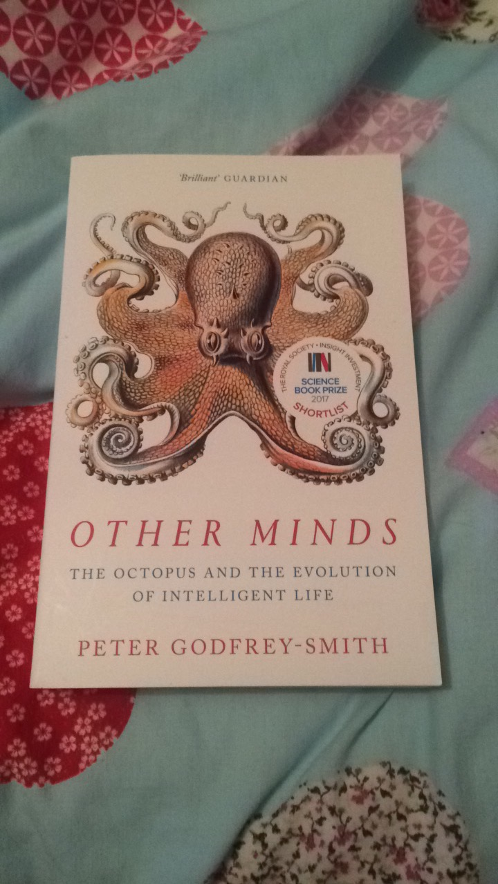 "A book called ""other minds, the octopus and the evolution of intelligent life"" by Peter Godfrey-Smith, on a bed sheet with hearts on it."