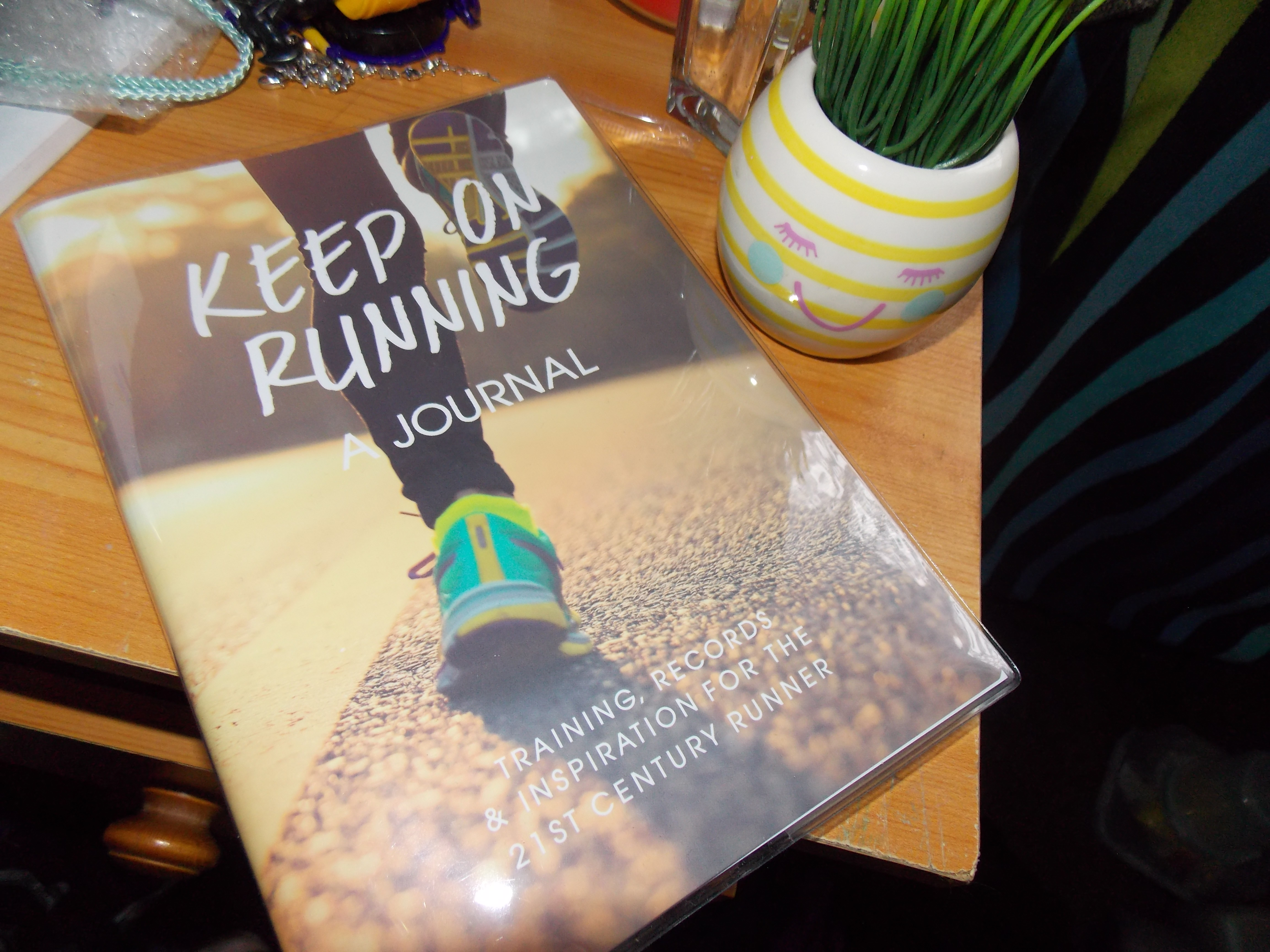 """A product picture of a running journal, with the words on front that say """"keep on running, a journal, training records & inspiration for the 21st century runner"""" and a picture of running legs/shoes. Taken on a wooden table with a stripey yellow and white plant pot with a pink smiley face."""