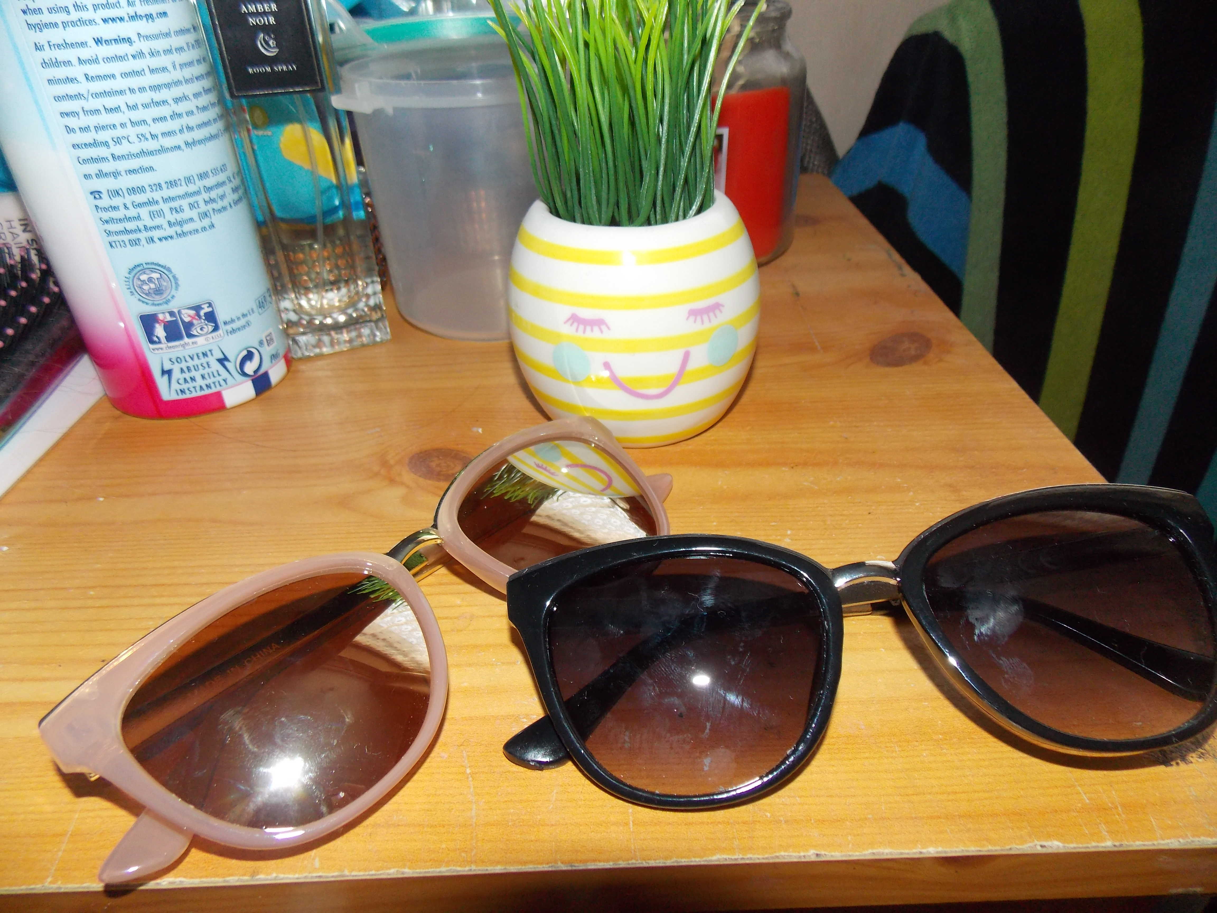 Two pairs of sunglasses. One pair is pink and gold, and the other are black.
