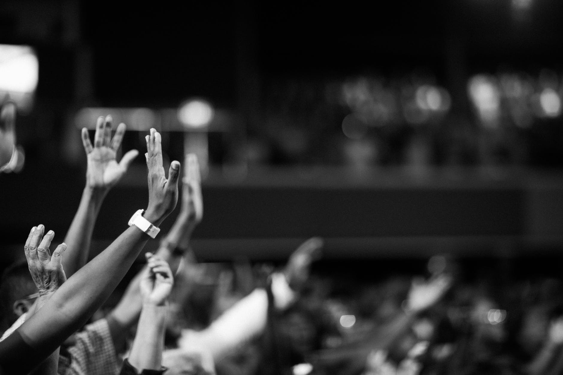 A black and white image of a crowd of people at a concert with their hands in the air.