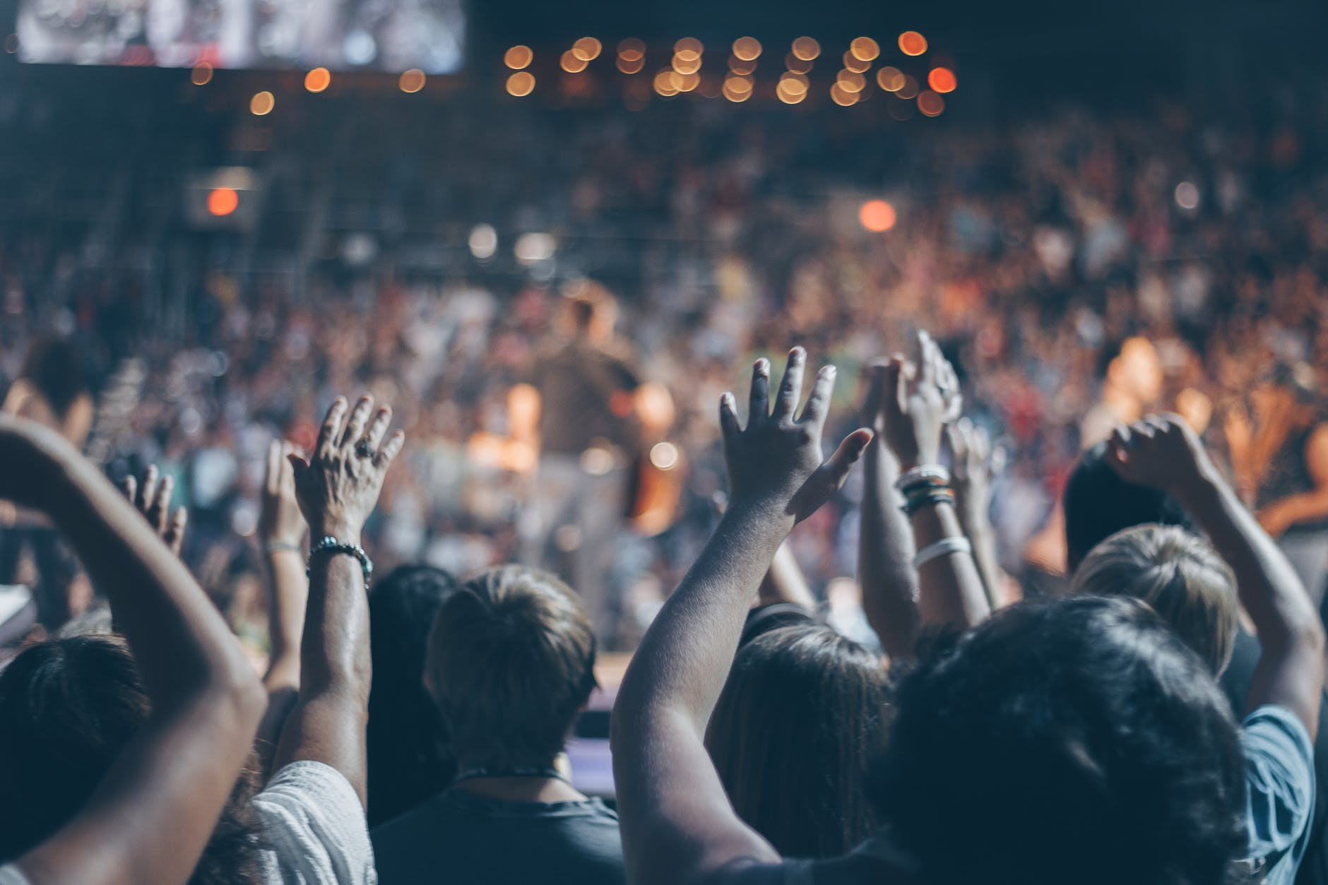 A crowd of people at a concert in the standing section with some with their hands in the air.