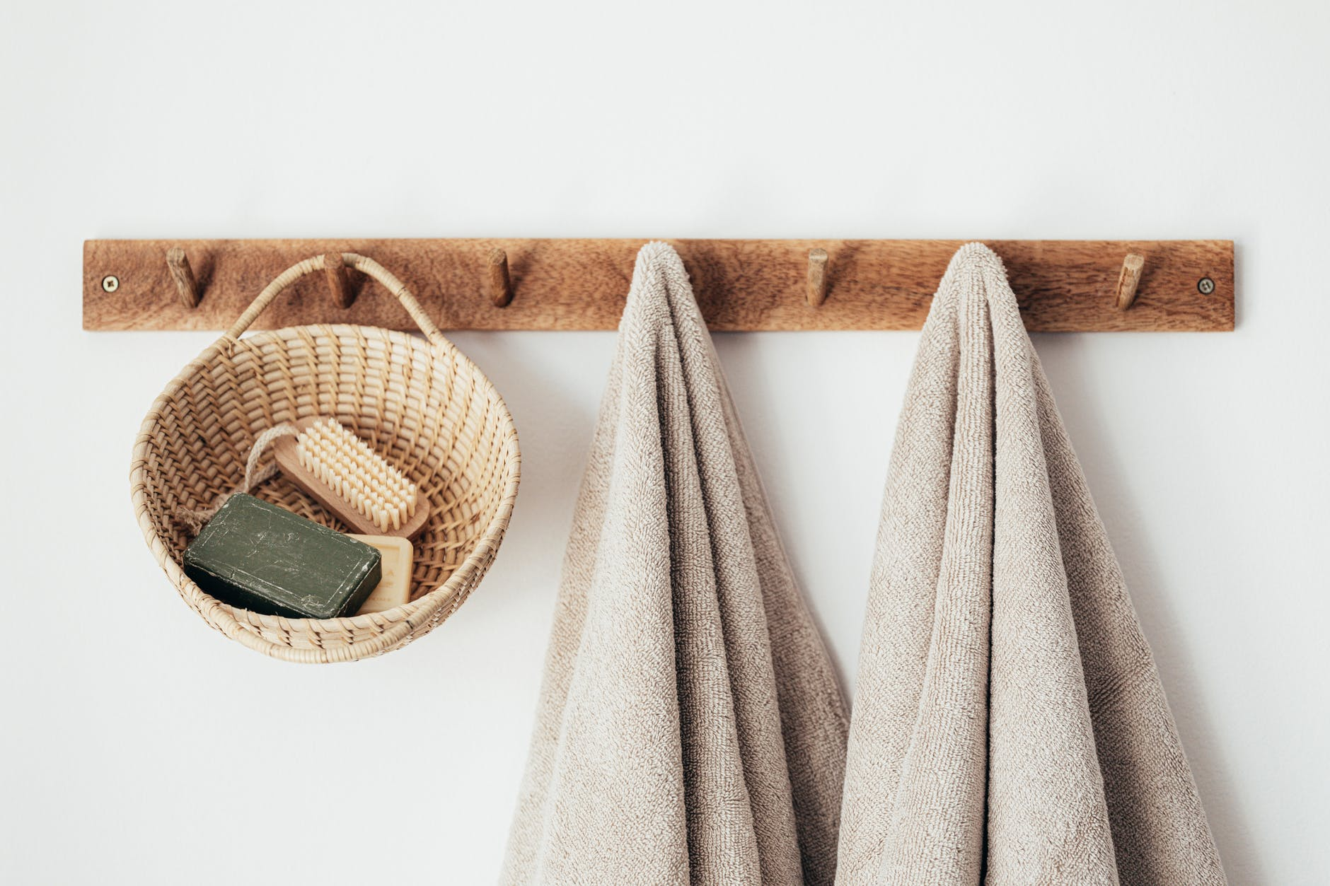 Some wooden hooks holding up some clothes and a wooden basket