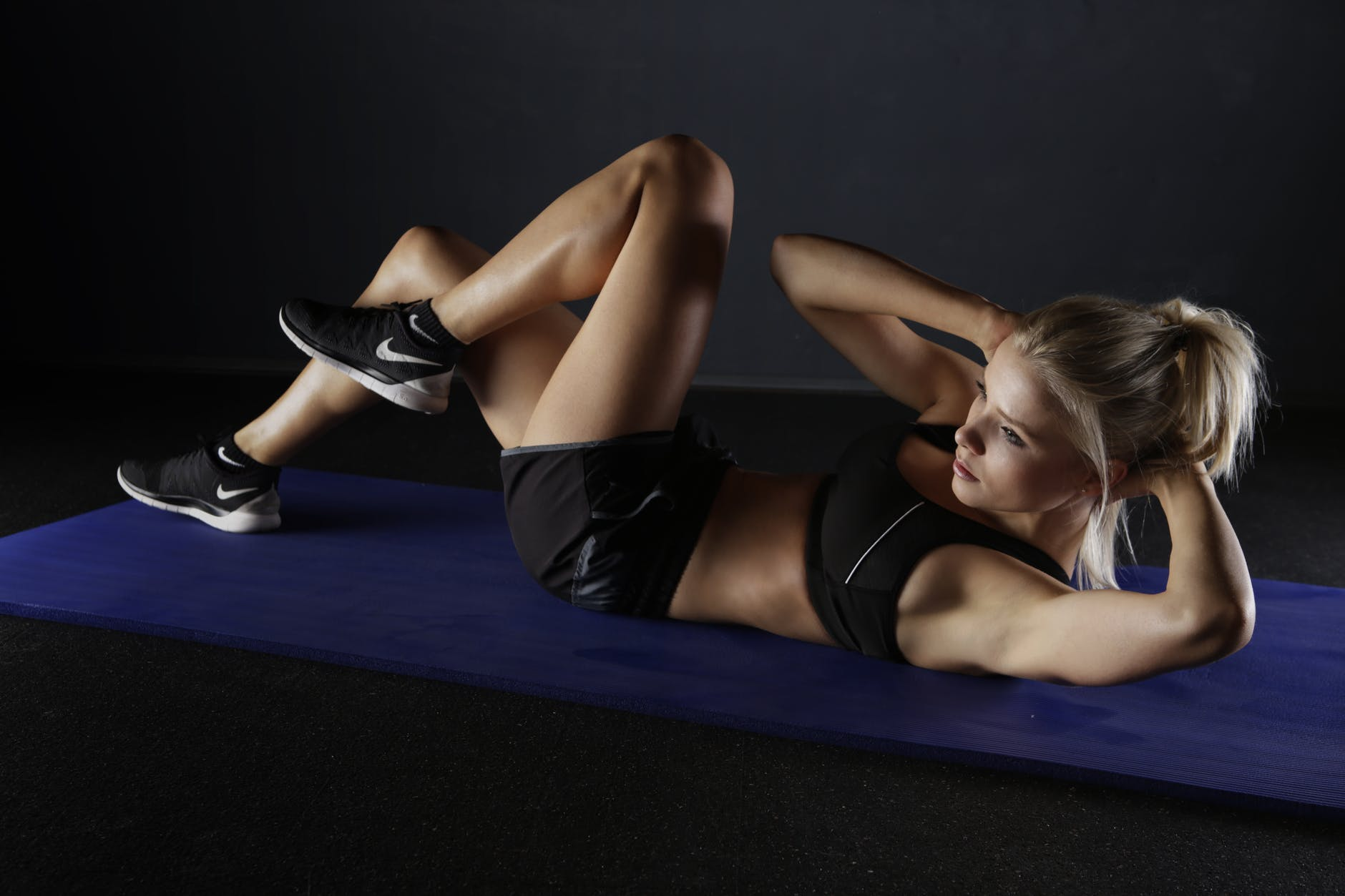 A woman doing bicycle crunches on a yoga matt in a black sports bra and shorts, and black nike trainers.
