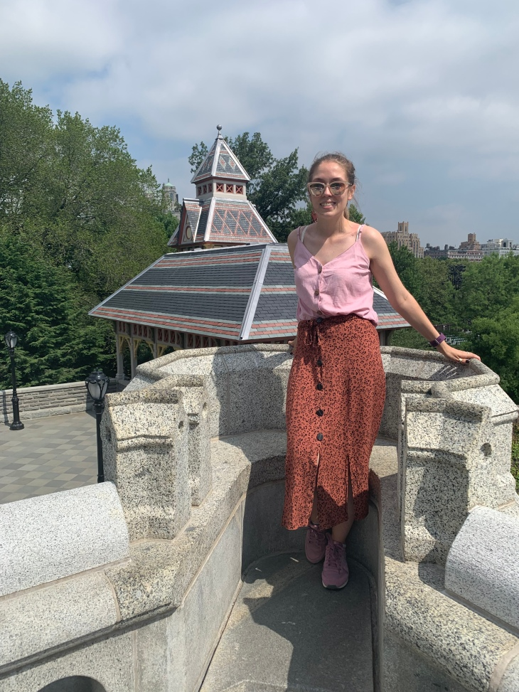 A woman with her hair tied up in a pink top and long skirt, standing on top of a castle in Central Park in New York