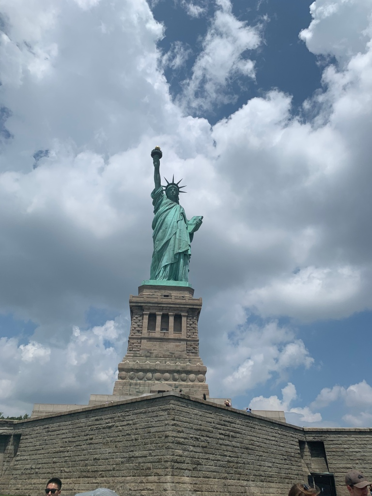 A picture of the Statue of Liberty  standing in front of it.