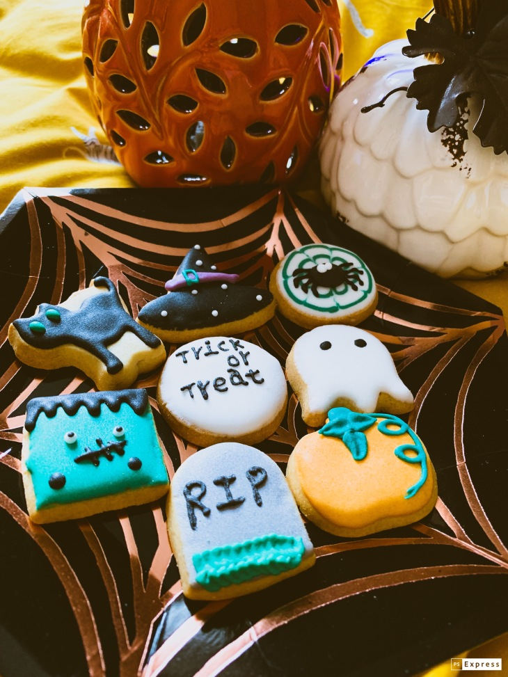 A plate full of Halloween themed shortbread biscuits with icing on them.