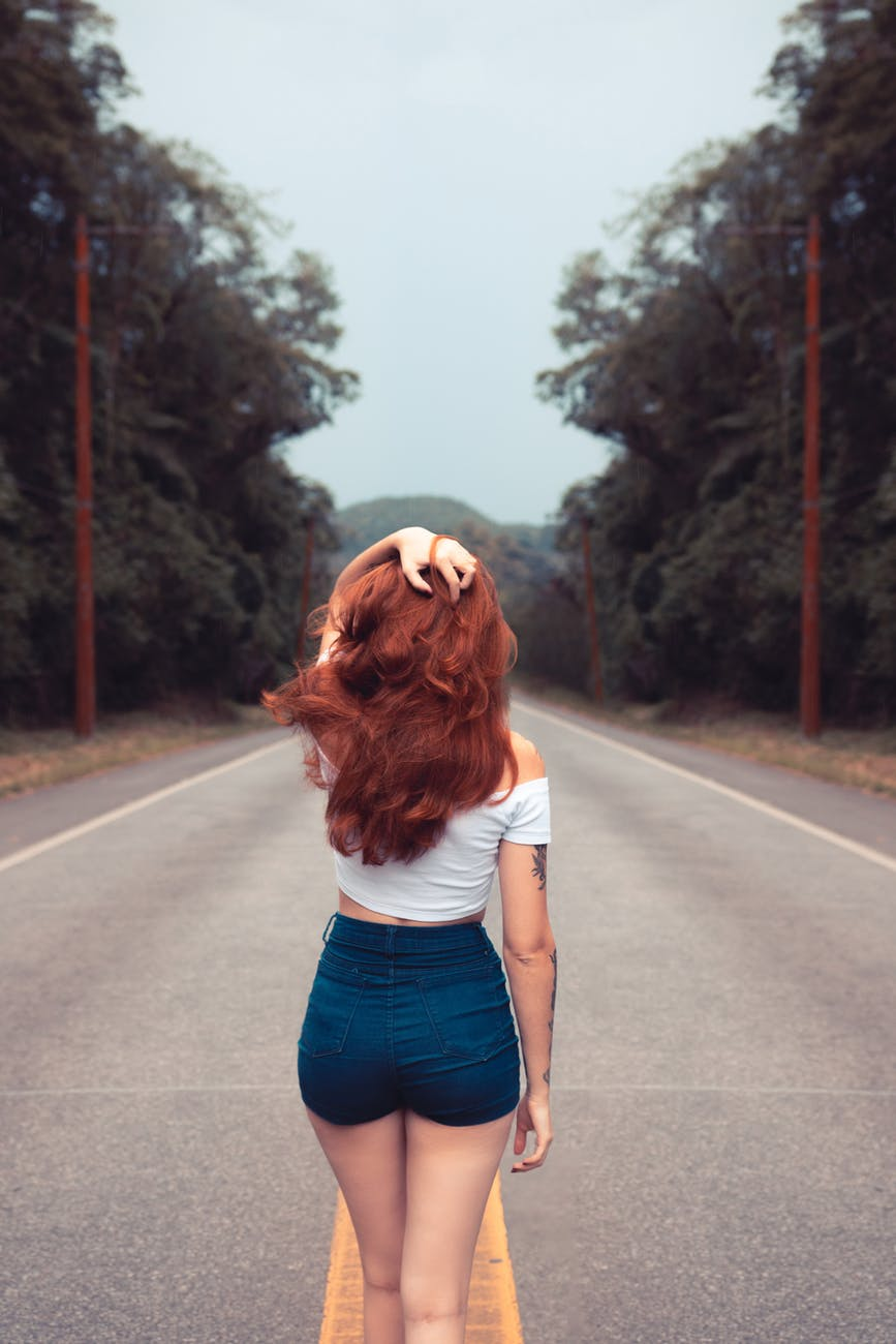 A woman with beautiful ginger hair in a white crop top and dark blue jeans standing in the middle of a road looking forwards with a forest either side