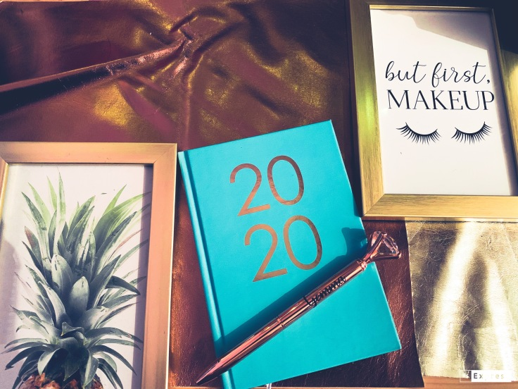 """A golden background with a 2020 diary and a fake diamond pen. Two golden frames with one picture of a pineapple and one picture of a """"but first makeup"""" and pictures of eyelashes."""