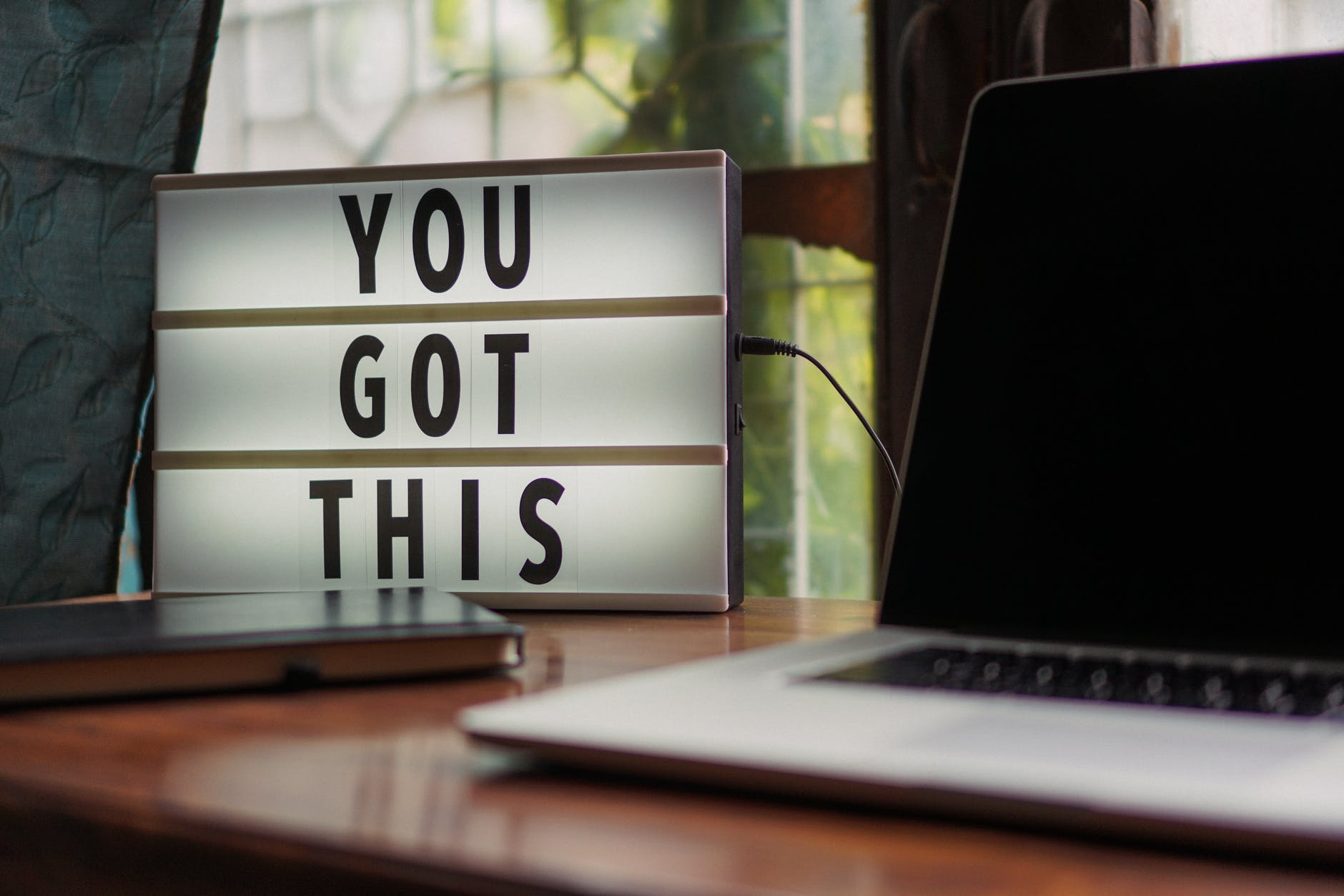 """A light up sign box that says """"you got this"""" on it, next to a blank screen laptop and a notepad."""