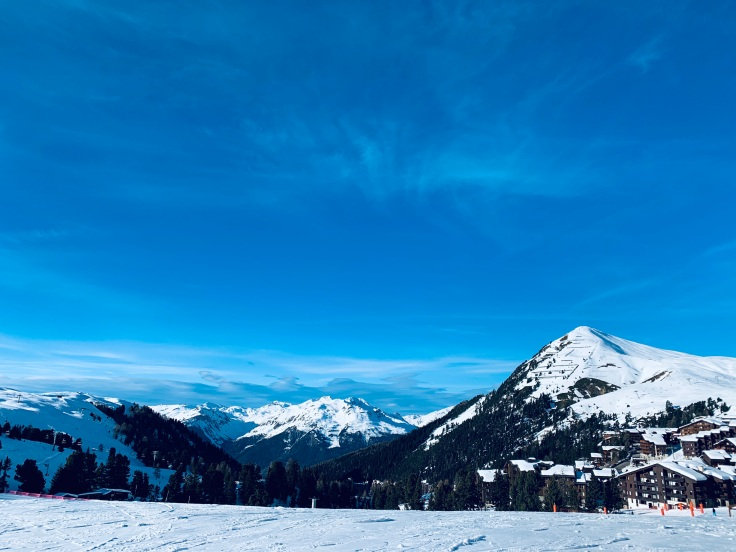 A view of the top of the mountains in La Plagne, France the French Alps, including ski chalets and snow mountains.