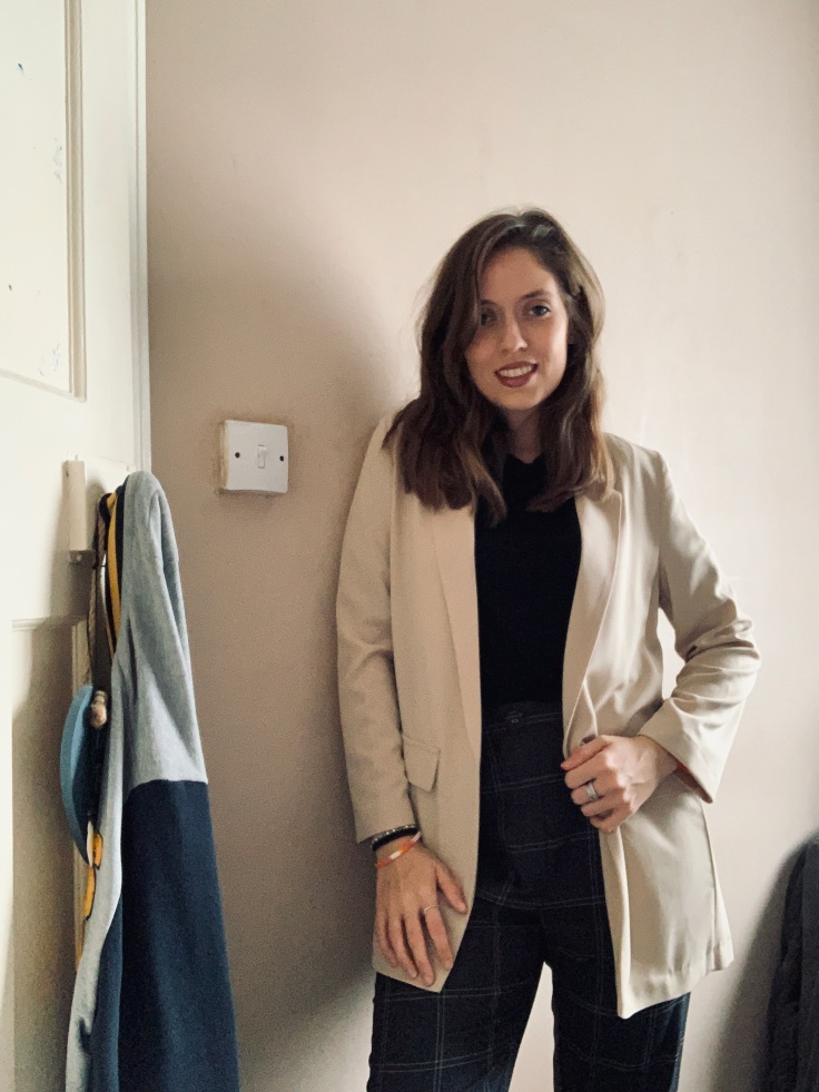 A woman in business attire wearing a cream blazer, checked trousers and a black top, with make up and jewellery on. Standing against a cream wall.