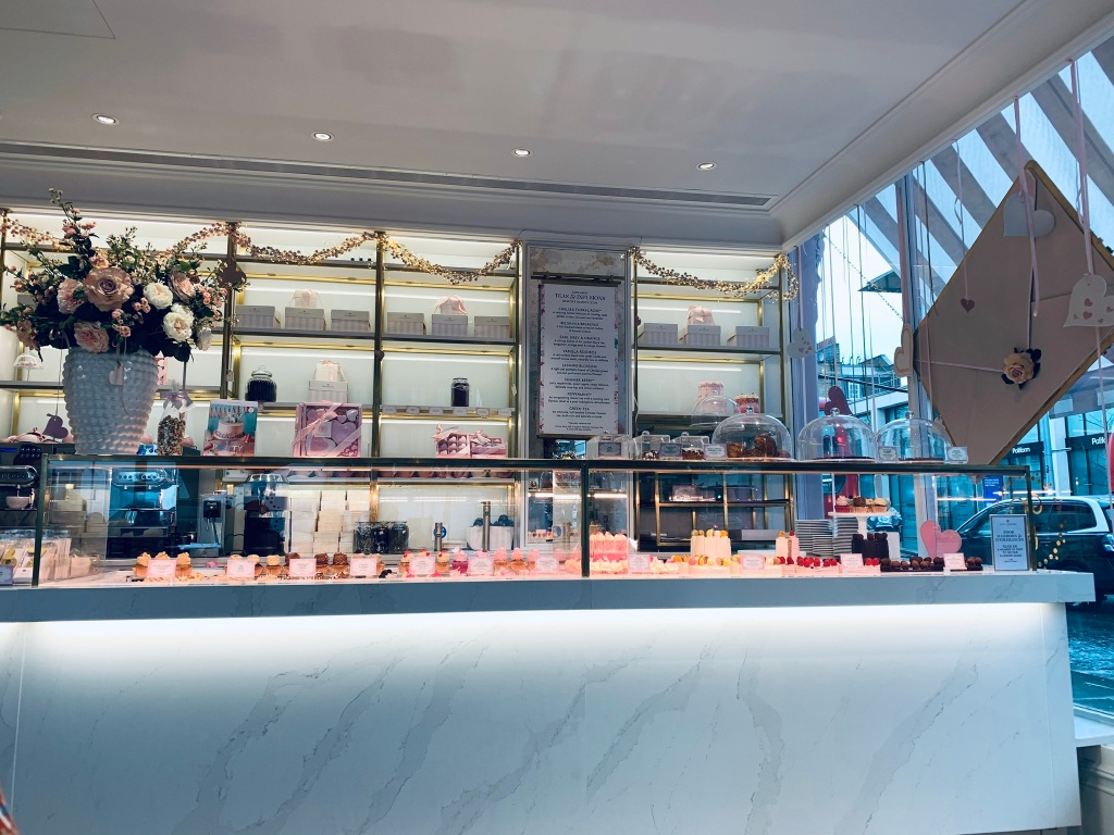 "Inside the London, Chelsea cafe ""Peggy Porschen"" counter and decoration, showing a selection of cakes and treats."