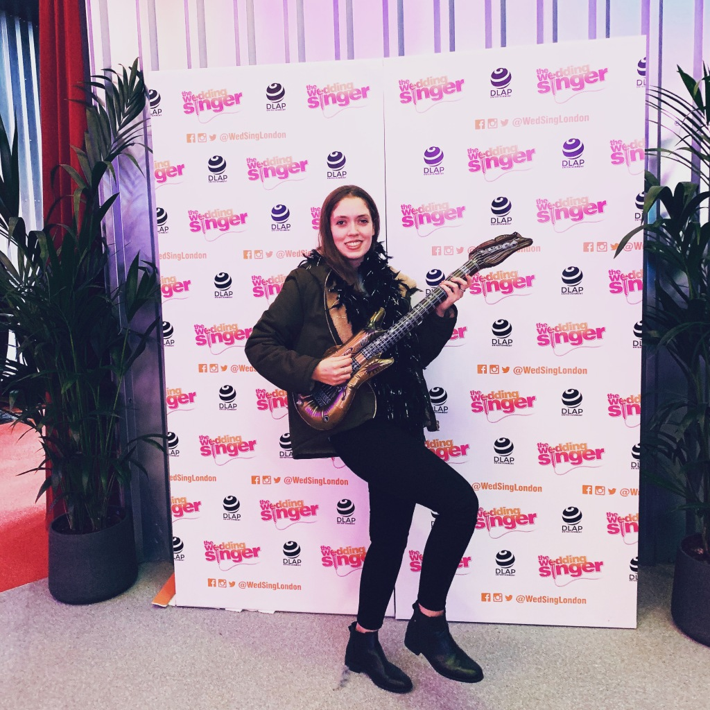 "A woman holding an inflatable guitar in a rock pose in front of a display at a theatre show ""The Wedding Singer""."