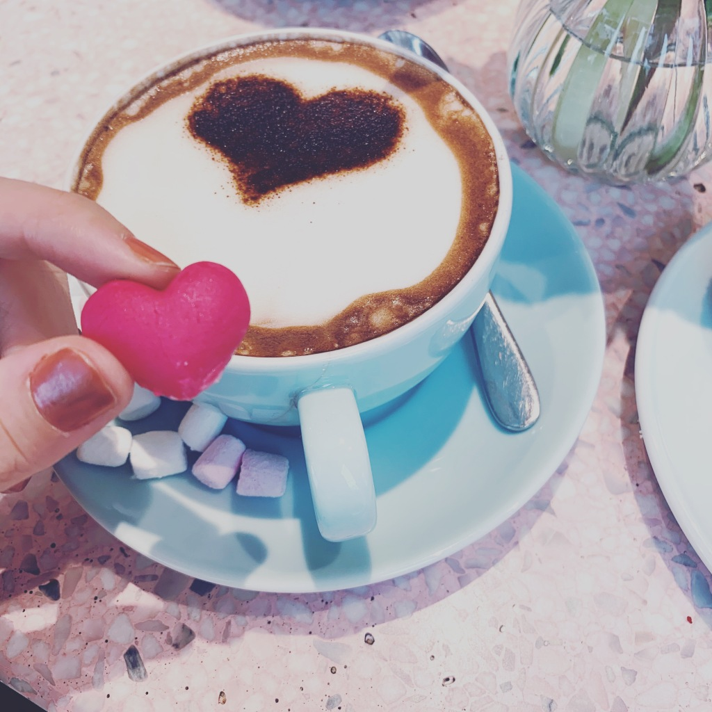 "A hot chocolate with a heart shaped biscuit and marshmellows, inside the ""Peggy Porschen"" cafe in London."