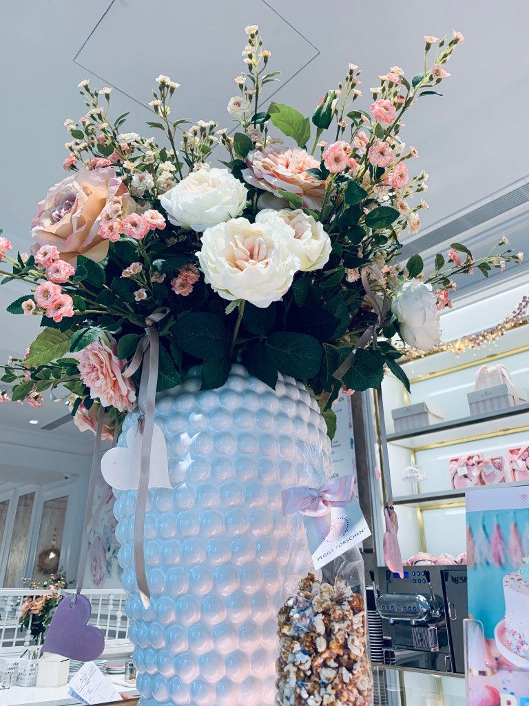 "Giant bouquet of pink and white flowers in a white vase, inside the ""Peggy Porschen"" cafe London."