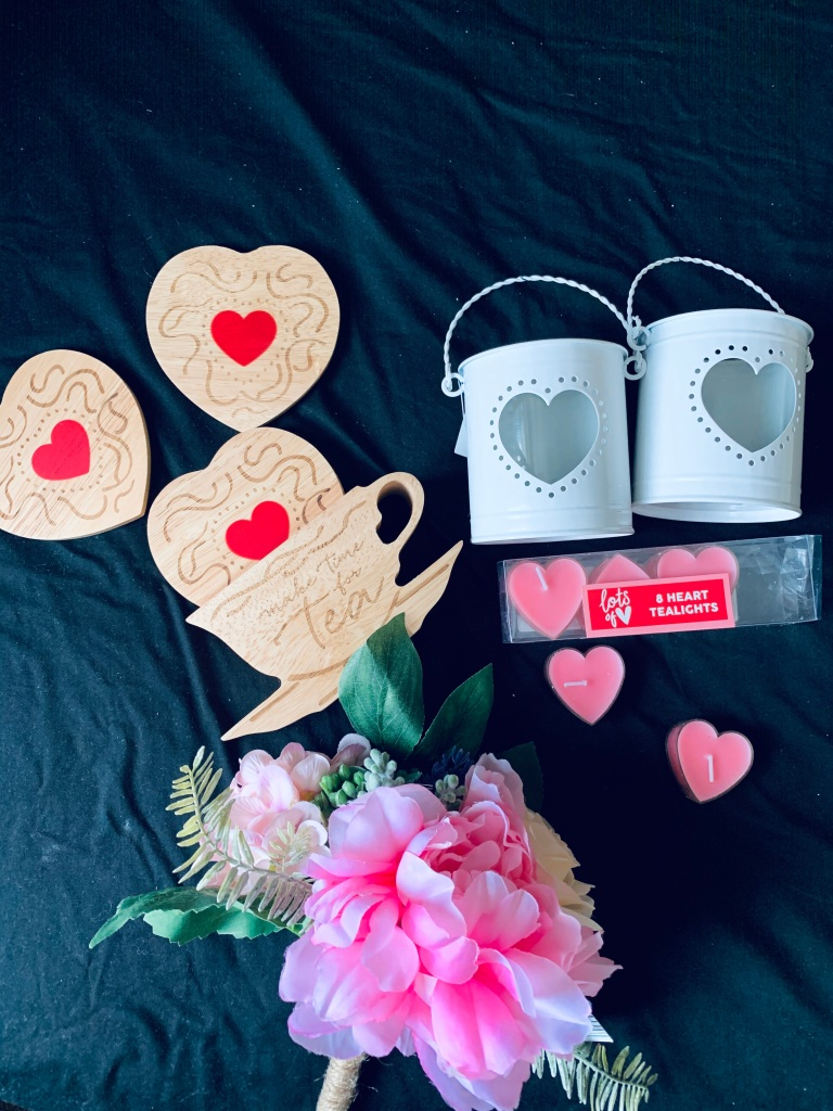 A collection of wooden tea coasters in a wooden teapot holder, two white tealight holders with pink heart shaped tealight candles underneath, and a bunch of pink flowers.