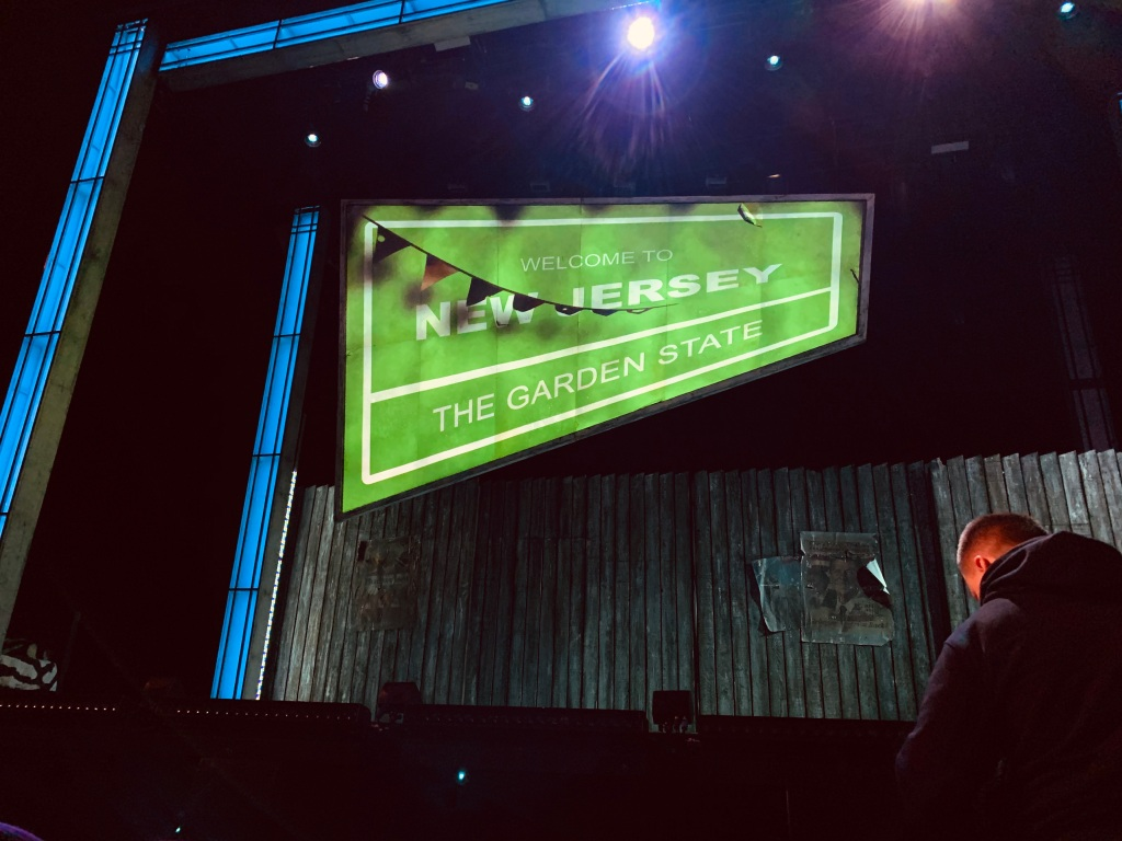 "A prop from the theatre show ""The Wedding Singer"" in London saying ""Welcome to New Jersey, The Garden State"" on the stage."