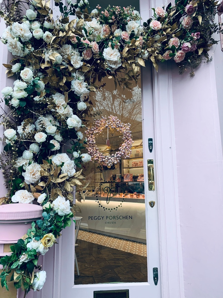 "The flower bouquet decorated door of London, Chelsea cafe/bakery ""Peggy Porschen"" with a pink letter box."