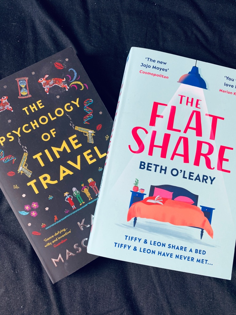 "Two different reading books, ""the psychology of time travel"" and ""the flat share"" placed next to each other."