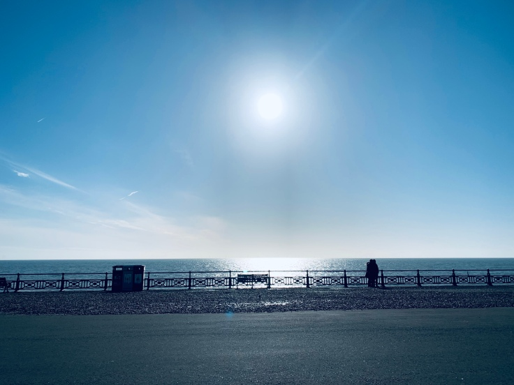 A view of Brighton beach with the sun shining.