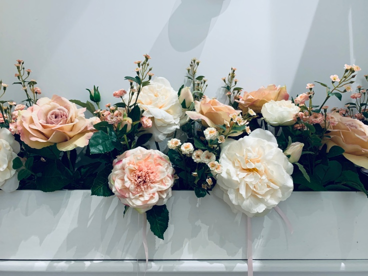 A display of different kinds of pink and white flowers in a rectangle vase.