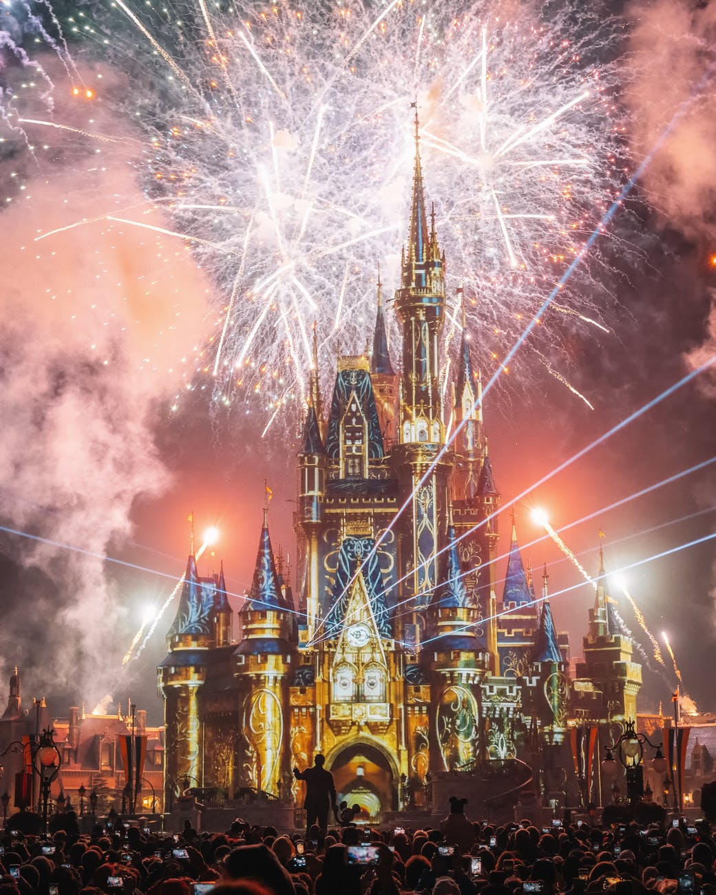 The Disney castle with crowds of people and fireworks going off all around it.