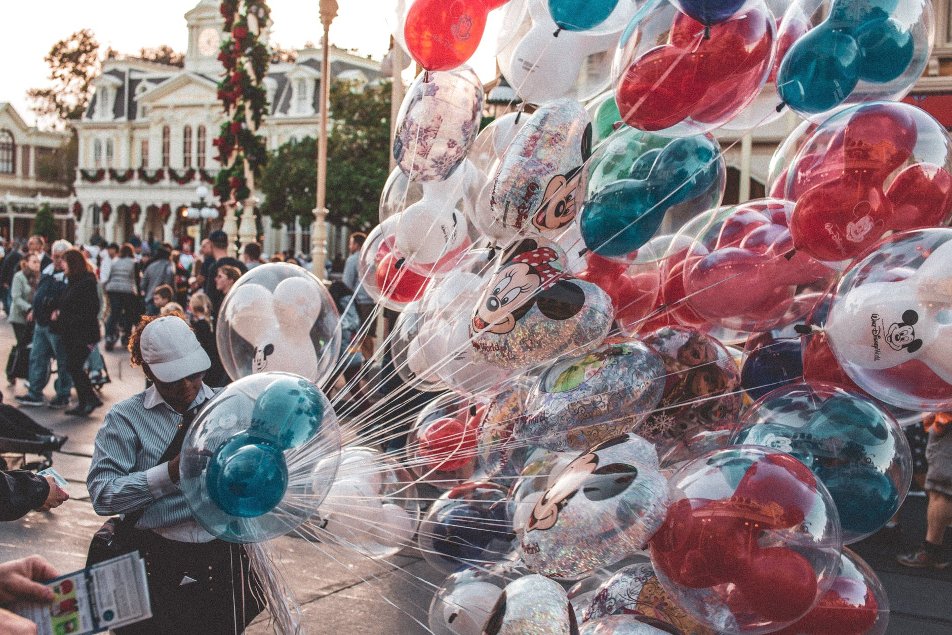 A selection of Disney balloons from Disney Land Pairs in a crowd full of people.