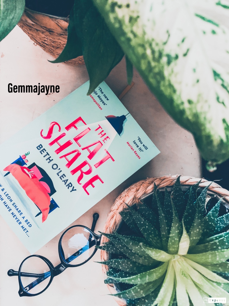 """A white marble background, with a book placed diagonally to the left called """"the flatshare"""" by """"Beth O'Leary"""". To the right of the book is a green plant and some black glasses. At the top right hand corner is a green leaf."""