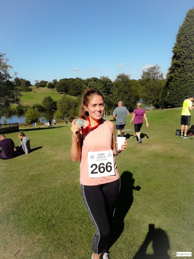 The Leeds castle race featuring a woman holding up her medal, wearing a pink nike sleeveless top, and black leggings with the park and fields in the background.
