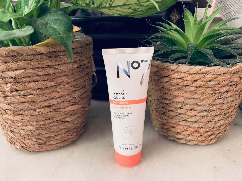 """""""No7 peel-off mask"""" product placed in the middle placed next to two plants either side in brown wooden baskets."""