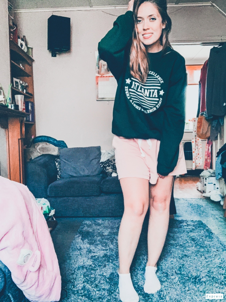 "A woman wearing a green jumper with the words ""Atlanta"" written across the middle, and pink shorts with white socks standing in her living room."