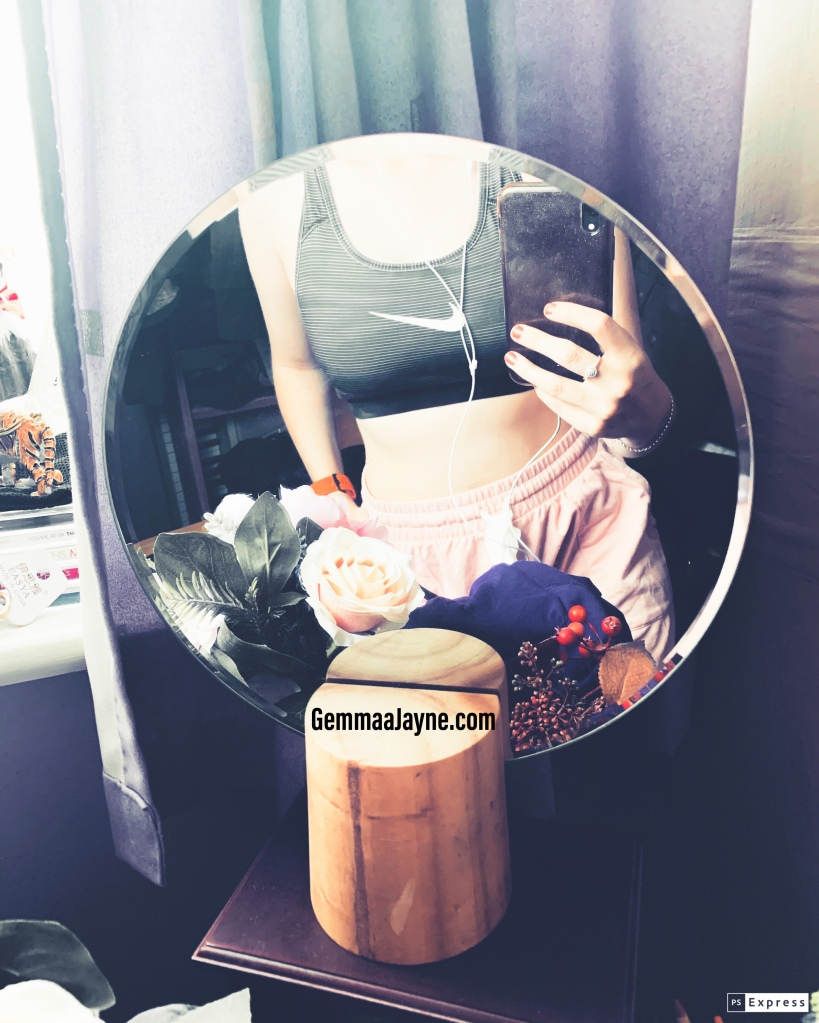 A mirror selfie of a sports bra and pink shorts, showing a toned tummy in the mirror. There is also flowers and the jewellery box that the mirror is standing on.