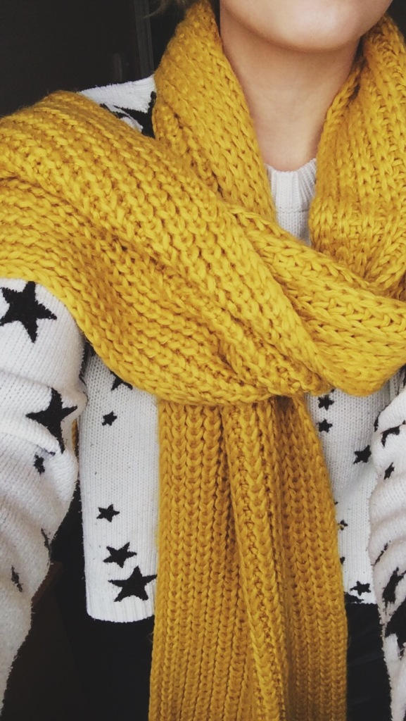 A yellow scarf, wrapped around a person wearing a white jumper with black stars on it.