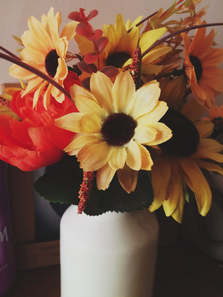 Fake flowers of yellow, red and oranges in a cream vase.