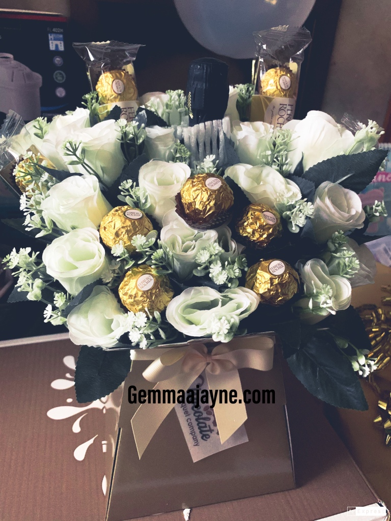 A bouquet of fake white roses, with Ferrero Rocher and a bottle of Prosecco in between them.