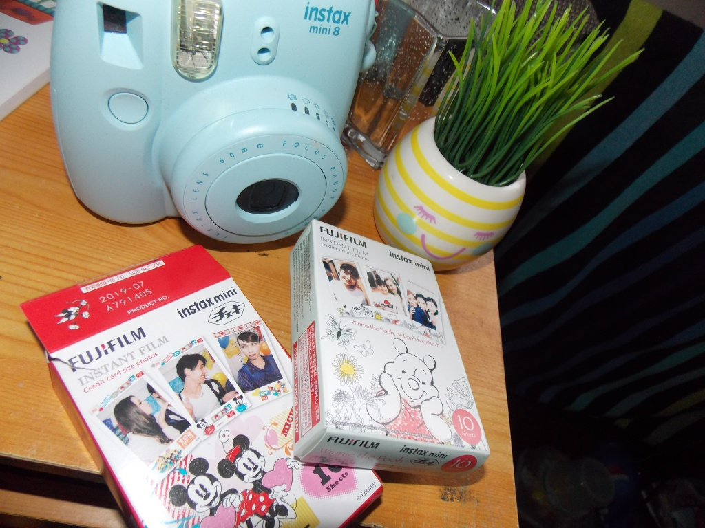 An Instax mini 8 blue camera with instax mini fujifilm disney edition. One is winnie the pooh border, and the other mickey and minnie mouse border.
