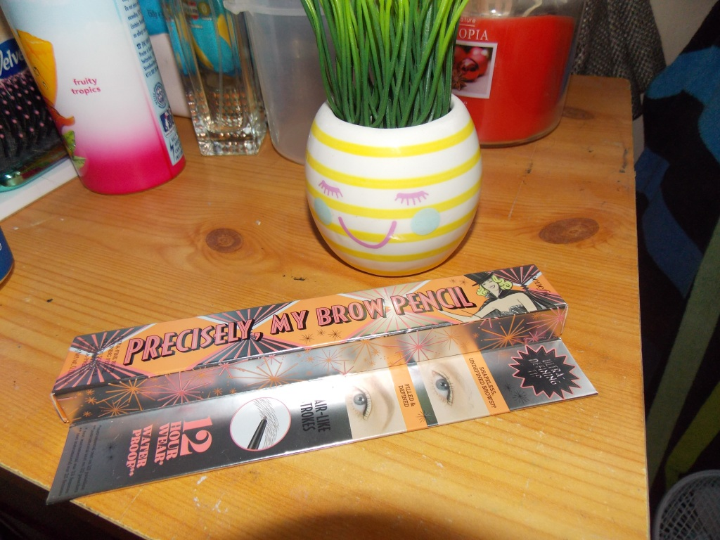 A product picture of an eyebrow pencil from the brand Benefit, in front of a stripey yellow and cream fake plant pot with grass coming out the top.