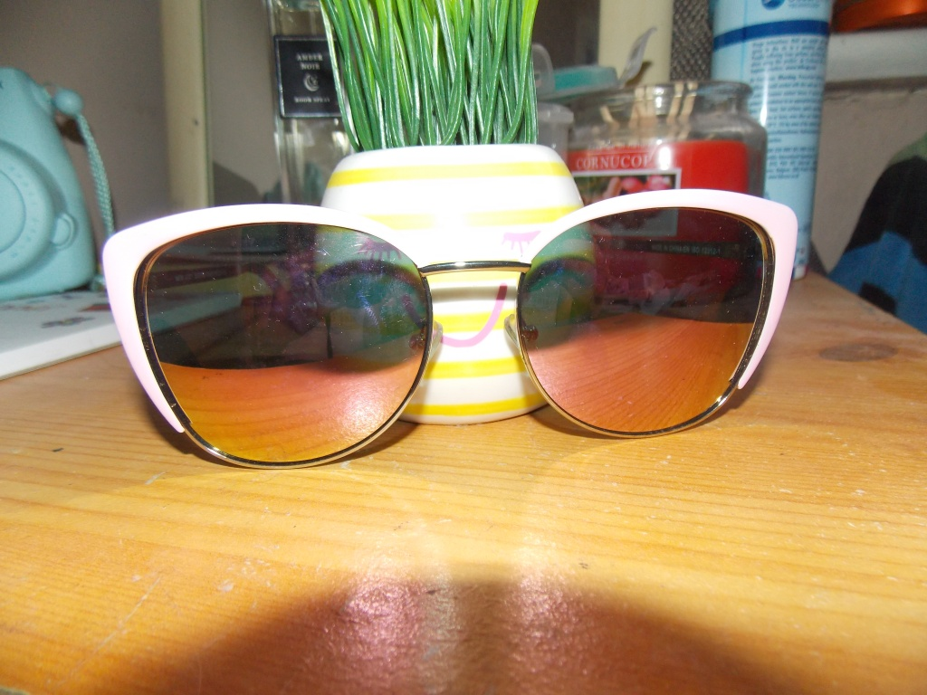 A product picture of a pair of sunglasses, with a pink line around the top.