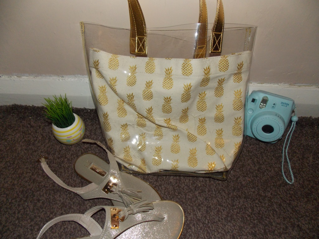 Product picture of a cream reusable bag with golden pineapples on it, and a see through bag over it. A blue Instax camera next to it, a stripey cream and yellow plant pot and shiny cream flip flops.