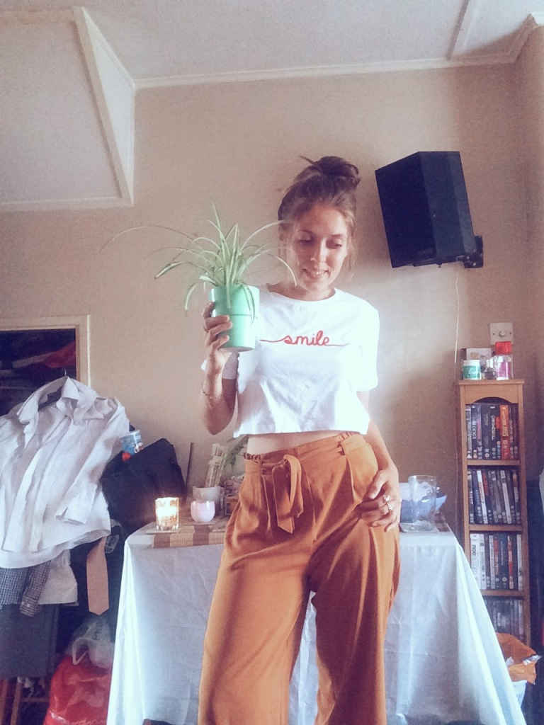 """A woman standing holding a green plant whilst wearing bright yellow trousers and a white top with the words """"smile"""" on it in red text. Standing in the living room in front of a table"""