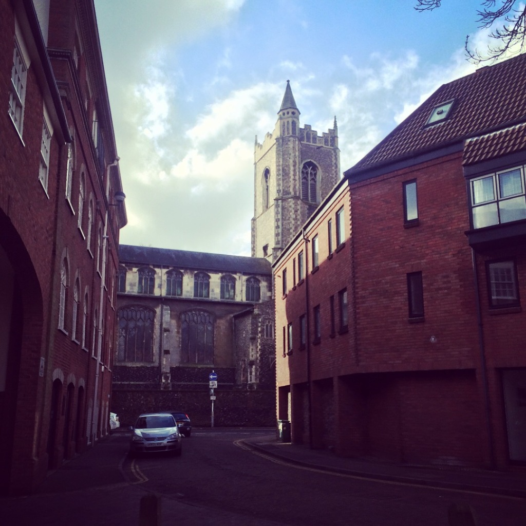 A street in Norwich with a Cathedral in the background coming out of the top of the buildings.