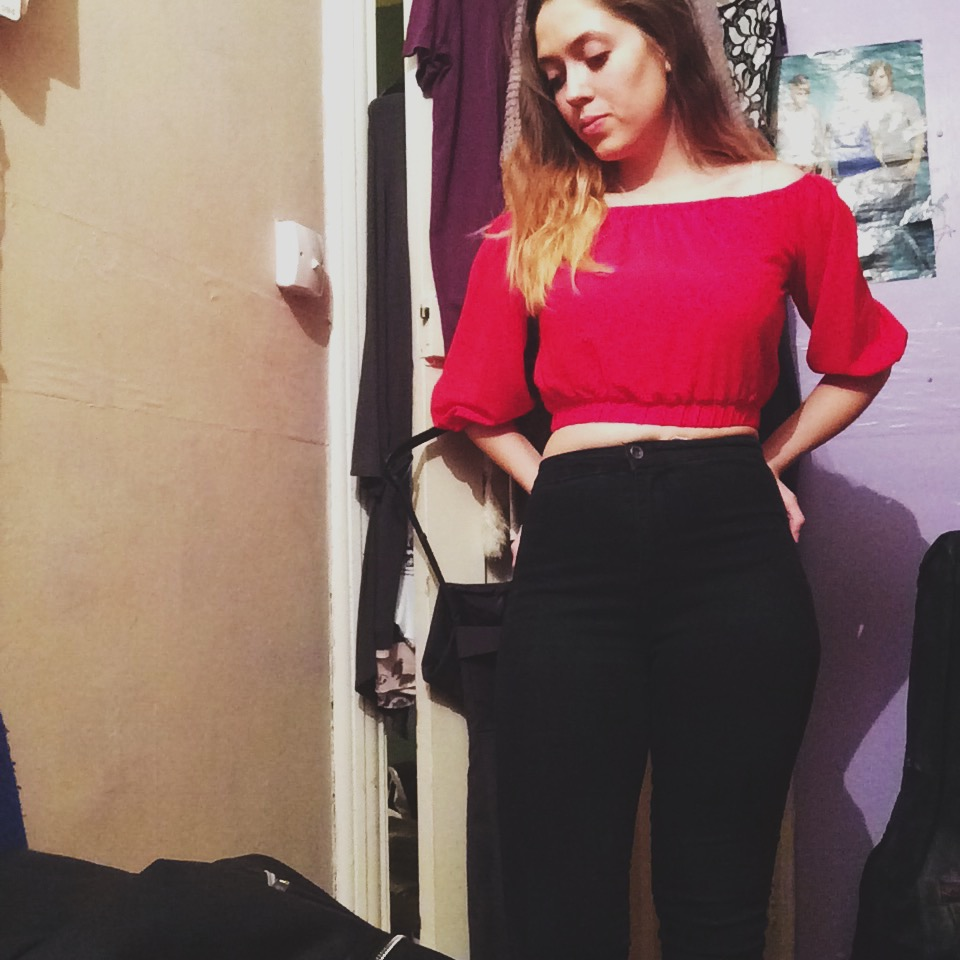 A woman wearing a cropped off the shoulder red shirt and skinny black jeans with her blonde/brown dip dyed hair down and standing in her bedroom.