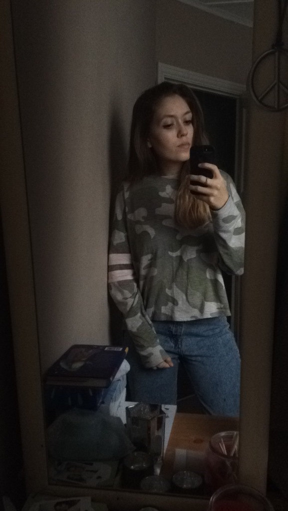 A woman wearing a long sleeved green camo top, with blue mom jeans in a mirror selfie.