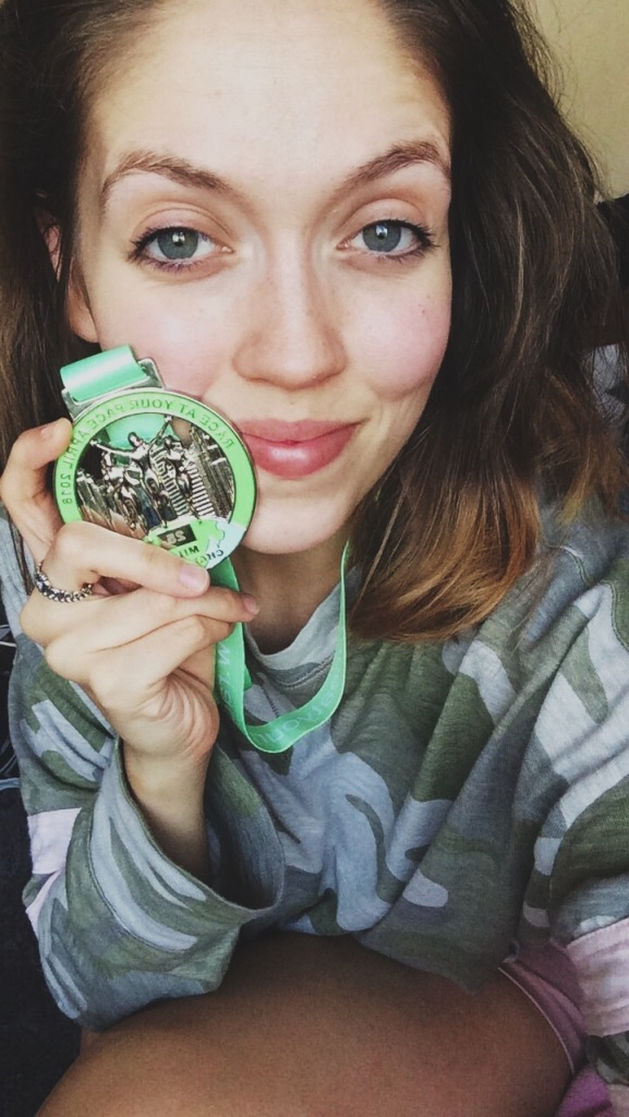 A woman holding a green running medal up whilst taking a selfie