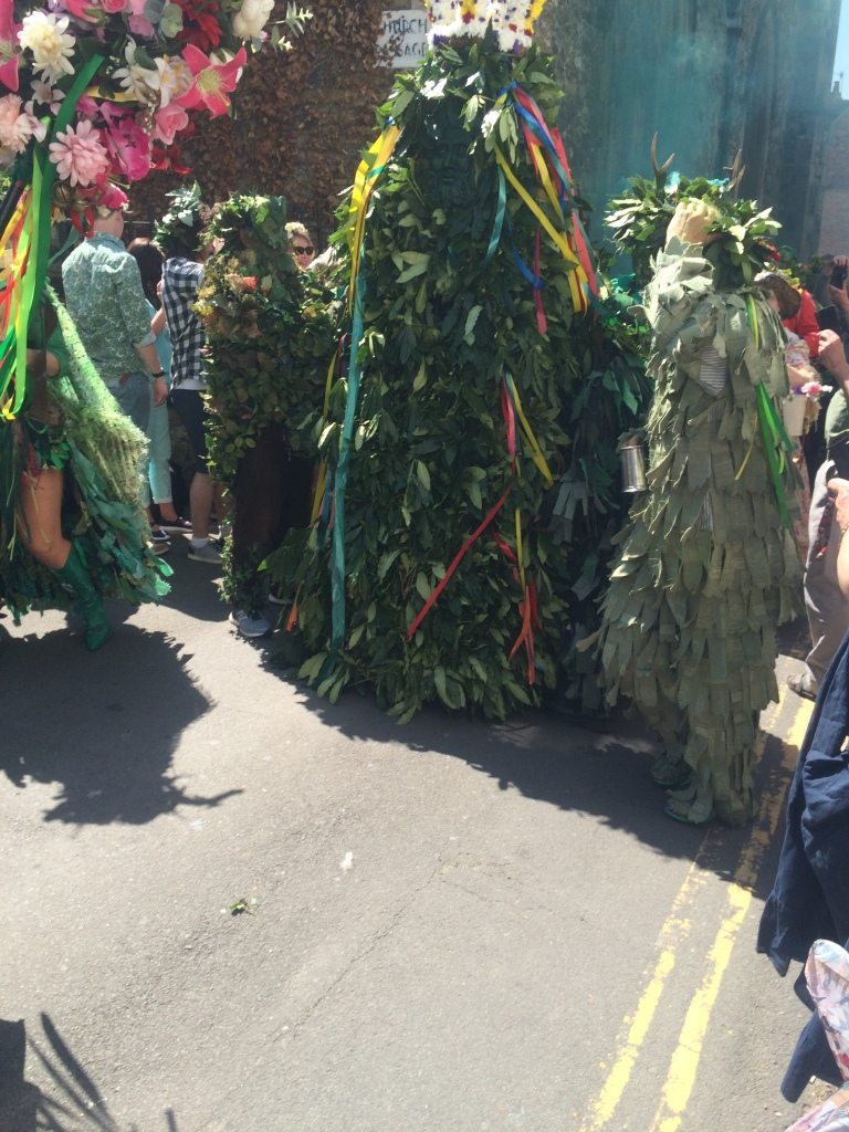 A picture of Jack the green from May day parade in Hastings in a crowd of people.