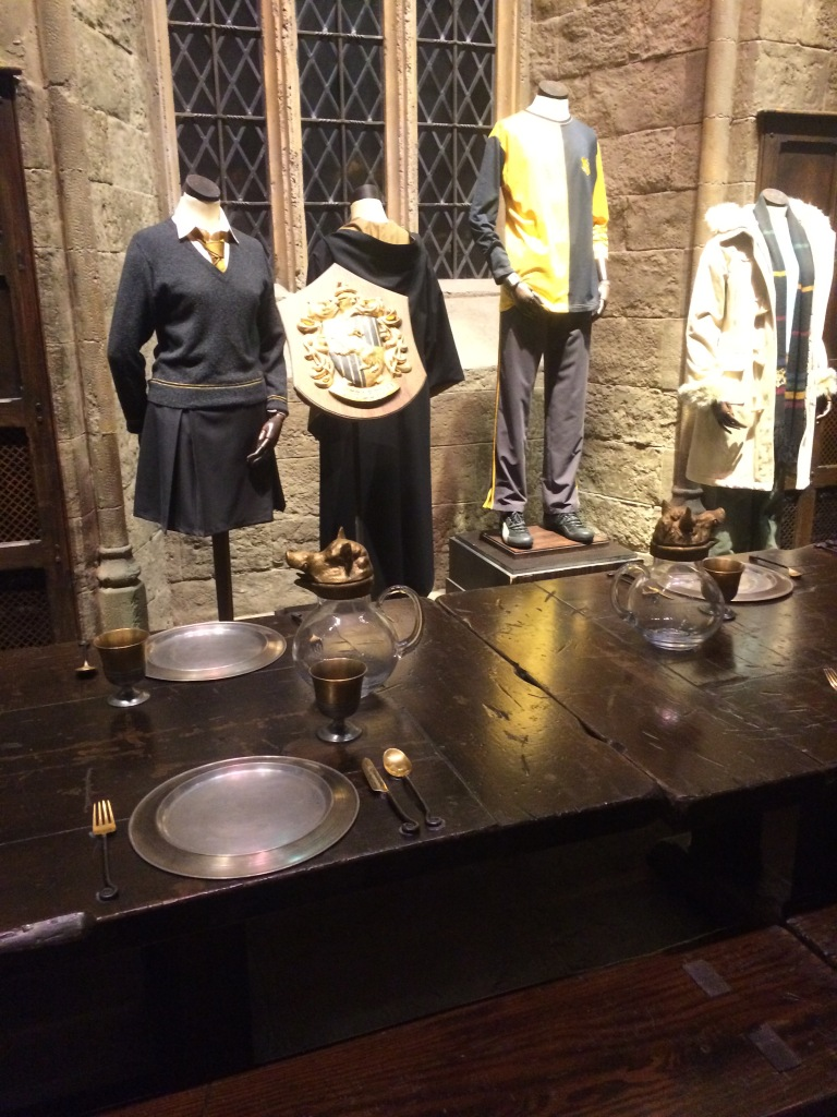 Photo from the Harry Potter Studies tour in London, showing the crest of Hufflepuff house and the uniforms, as well as part of the table in the Great hall.