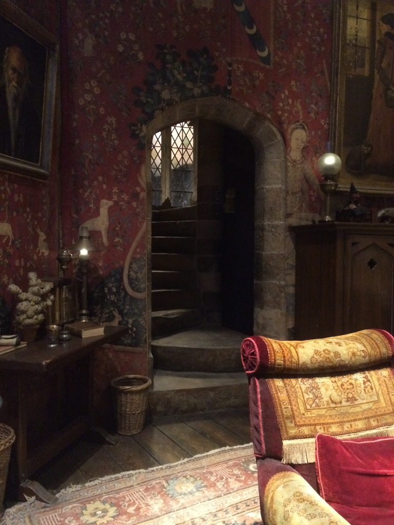 The Griffindor living room, and stairs, with the paintings  and a chair at the set of Harry Potter Studios.