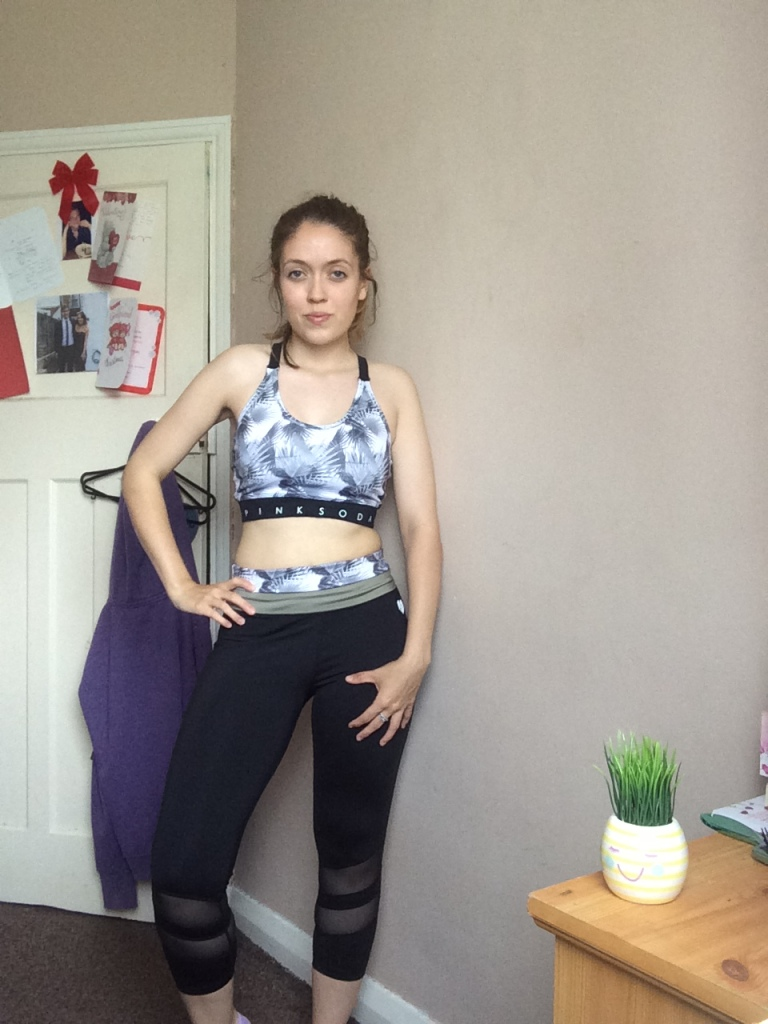 A woman in gym gear, wearing a grey and black sports bra and leggings posing in her bedroom